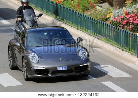 Monte-Carlo Monaco - May 18 2016: Beautiful Woman Driving an Expensive Porsche 911 Carrera S on Avenue Princesse Grace in Monte-Carlo Monaco in the south of France