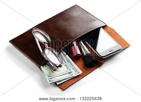 Leather purse with mobile phone, glasses, makeup brush and dollar banknotes, isolated on white