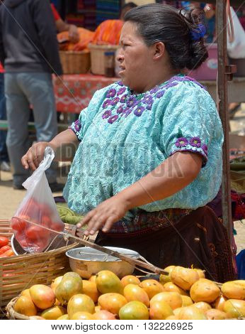 CHICHICASTENANGO GUSTEMALA APRIL 29 2016: Portrait of a Mayan woman saling fruits and vegetables. The Mayan people still make up a majority of the population in Guatemala,