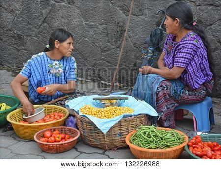 CHICHICASTENANGO GUSTEMALA APRIL 29 2016: Portrait of a Mayan woman selling fruits and vegetables. The Mayan people still make up a majority of the population in Guatemala,