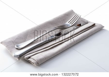 cutlery with linen napkin on white background