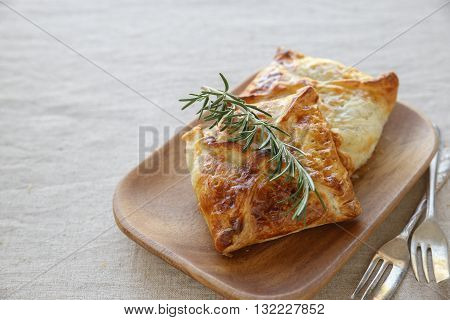 Homemade chicken puff pie on wooden plate, selective focus