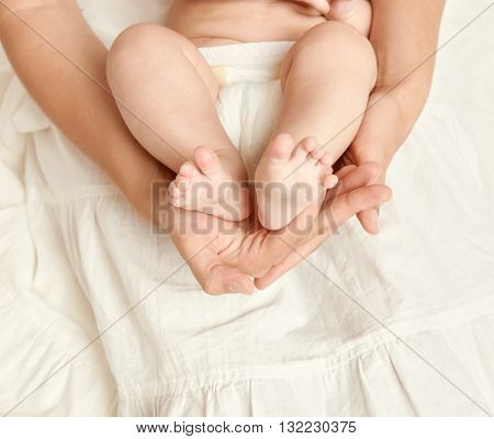 baby feet in mother hand, health care concept, body and skin, yellow toned