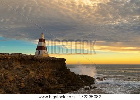 View of waves splashing rock at Obelisk, a historic landmark at Cape Dombey during sunset in Robe, South Australia