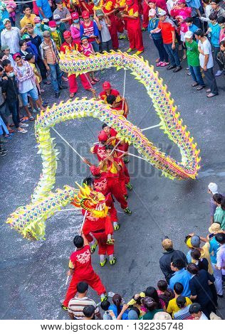 Binh Duong, Vietnam - February 22nd, 2016: Festival dragon dance Chinese Lantern with yellow winding control martial arts practitioners across street to cheers tourists around in Binh Duong, Vietnam
