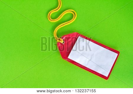 Rad plastic luggage tag isolated on green background