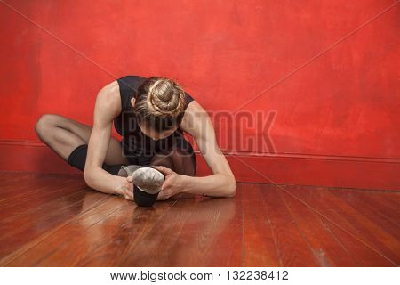 Young Ballerina Stretching In Studio