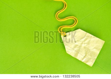 Blank yellow price tag isolated on green Price tag gift tag sale tag address label etc.