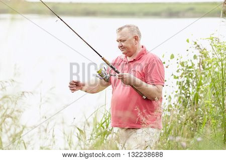 Middle aged man wearing polo shirt, setting up bait during summer angling on lake - fishing concept