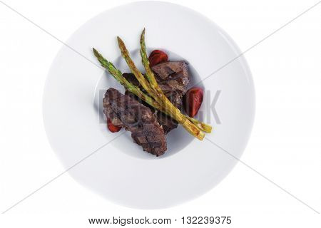 grilled red beef pork meat barbecue steak fillet with asparagus and hot pepper served on deep plate isolated on white background