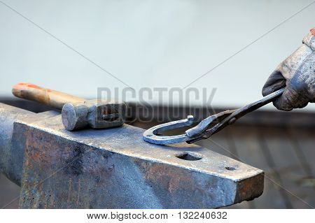Blacksmith forges a horseshoe for horse close up
