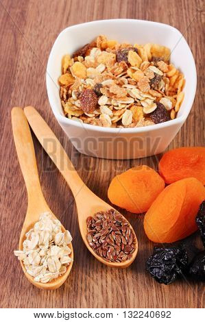 Portion of linseed and rye flakes on spoon dried fruits and muesli concept of healthy nutrition and increase metabolism ingredients with dietary fiber