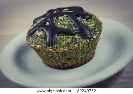 Vintage photo Homemade fresh muffin baked with wholemeal flour with spinach desiccated coconut and chocolate glaze delicious healthy dessert or snack