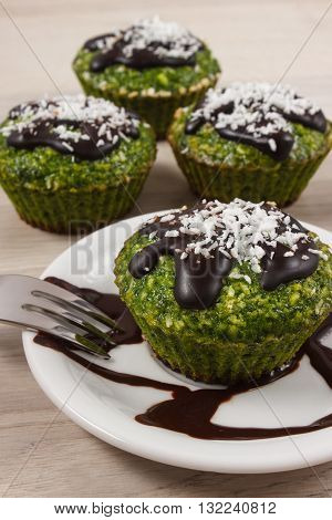 Homemade fresh muffins baked with wholemeal flour with spinach desiccated coconut and chocolate glaze delicious healthy dessert or snack