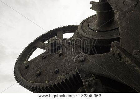 Single black painted cog wheel from an bygone industrial era set against a grey sky.
