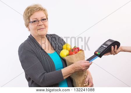 Elderly senior woman holding shopping bag with fruits and vegetables using payment terminal with credit card cashless paying for shopping healthy nutrition