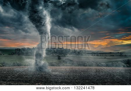 Black tornado funnel over field during thunderstorm