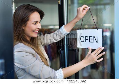Woman hanging open sign on door