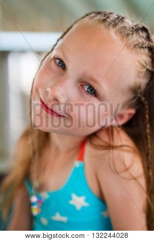 Casual portrait of little girl with Caribbean braids outdoors on summer day