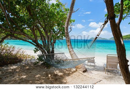Beautiful tropical beach with white sand, hammock, turquoise ocean water and blue sky at St John, US Virgin Islands in Caribbean