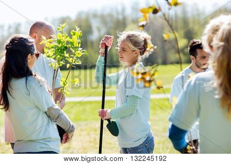 volunteering, charity, people and ecology concept - group of volunteers with garden tools planting trees and talking in park