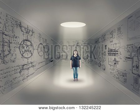 Young girl in center of a room looking up through a hole izolated in a room with a design drawn on the wall