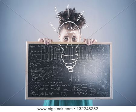 Young girl holding a blackboard with mathematical formulas and a light bulb. Idea concept