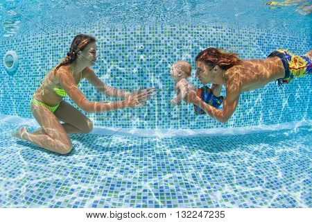 Child swimming lesson - baby with mother father learn to swim dive underwater in swimming pool. Healthy active family lifestyle physical exercise water sport activity with parent on summer holiday