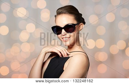 accessories, eyewear, fashion, people and luxury concept - smiling beautiful young woman in elegant black sunglasses over holidays lights background