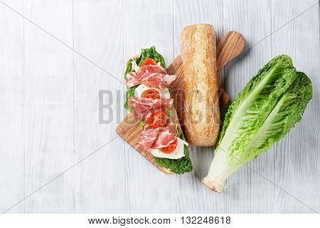 Ciabatta sandwich with romaine salad, prosciutto and mozzarella cheese over wooden background. Top view with copy space