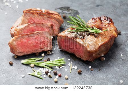 Grilled sliced beef steak with salt, pepper and rosemary on stone table