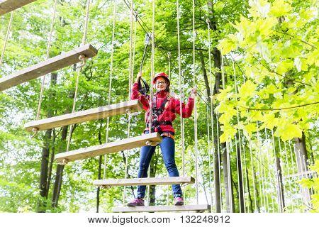Teenage girl, walking on rope bridge in climbing course enjoying the trill of the sport