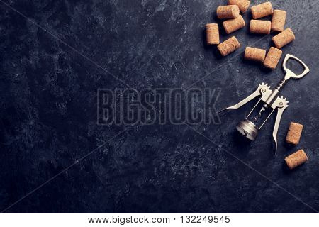 Wine corks and corkscrew over dark stone background. Top view with copy space. Retro toned