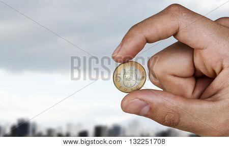Five euro coin between fingers