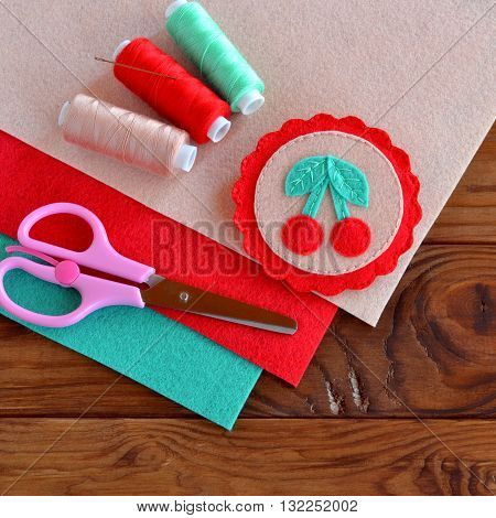 Summer felt brooch with embroidery. Felt brooch with red cherries and green leaves. Set of multicolored thread, pink scissors. Wooden background. Sheets of felt. Simple sewing project