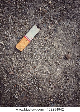 Burnt cigarette stub butt on dirty sand ground floor vintage effect