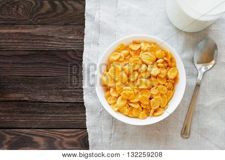 Tasty corn flakes in bowl with bottle of milk. Rustic wooden background with homespun napkin. Healthy crispy breakfast snack. Place for text. Top view flat lay.
