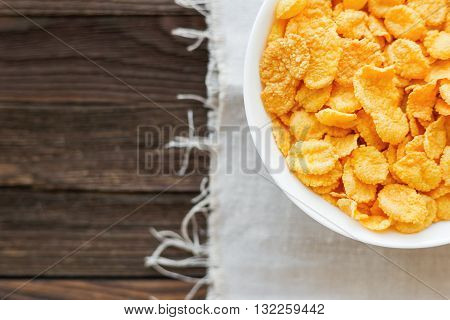 Tasty corn flakes in bowl. Rustic wooden background with homespun napkin. Healthy crispy breakfast snack. Top view flat lay. Place for text.