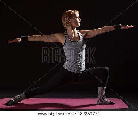 Young woman practicing yoga, Virabhadrasana / Warrior pose