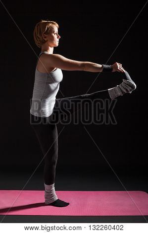 Young woman practicing yoga, Padangusthasana / Extended triangle pose