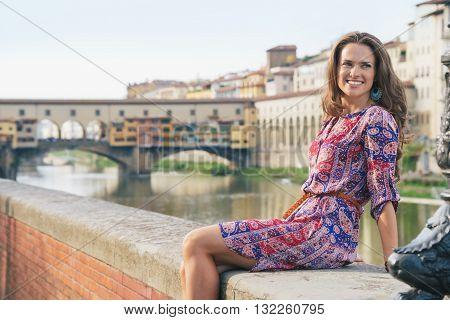 Smiling Woman Sitting On The Embankment Near Ponte Vecchio
