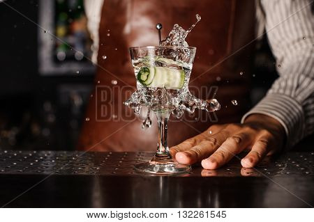 cucumber falling into the glass. barman on background