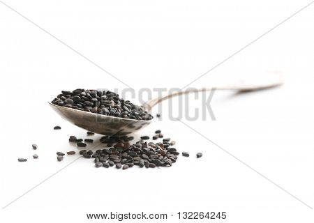 Black sesame seeds. Healthy sesame seeds in spoon  isolated on white background.