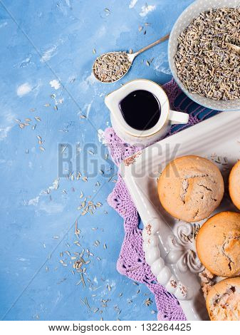 Lavender muffins with ingredients - lavender syrup milk and lavender flowers on blue textured background. Vertical image. Copy space