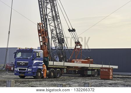 YSBRECHTUM, THE NETHERLANDS - JUNE 1, 2016: Photo of blue truck, carrying 23 m long driving piles, ready for being unloaded at construction site. Trucker is wearing orange safety overall.