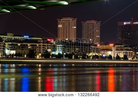 Bratislava, Slovakia - May 29, 2016 Night view from the riverbank of Danube on the new luxury part of Slovak capital - Bratislava. Lights line of a passing boat.