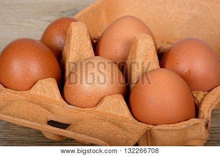 Six fresh brown eggs in a brown cardboard box