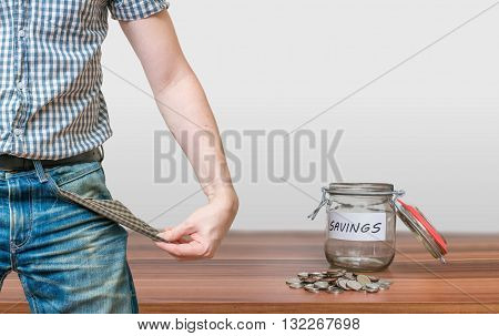 Man showing pocket as no money symbol and jar with coins.
