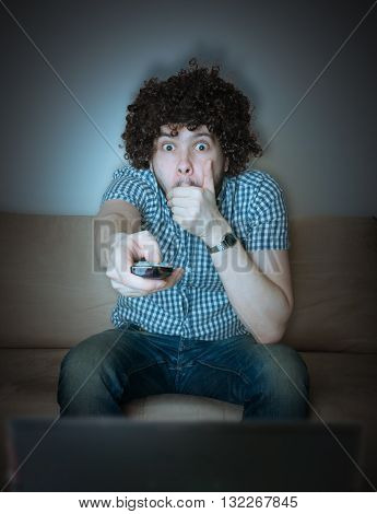Young Scared Man Is Watching Horror Or Thriller On Tv.