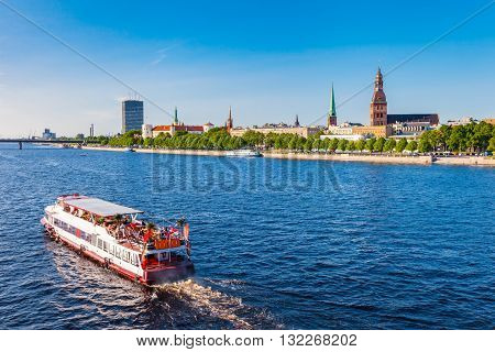Walking ship floats the river Daugava panoramic view of old Riga on background. Riga Latvia